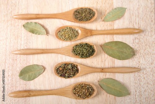Fotografie, Obraz  Wooden spoons with traditional Italian herbs for cooking on a light wood table
