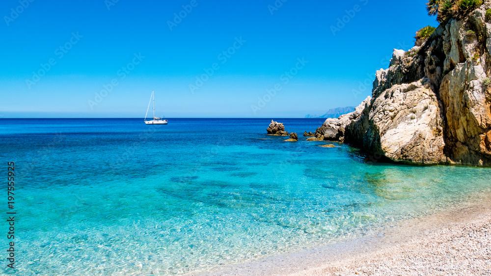 Fototapety, obrazy: A sailing boat into the turquoise Mediterranean Sea, at San Vito Lo Capo, Sicily, Italy.