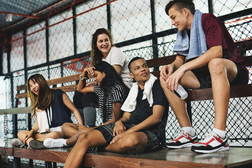 Group of young teenager friends sitting on a bench relaxing