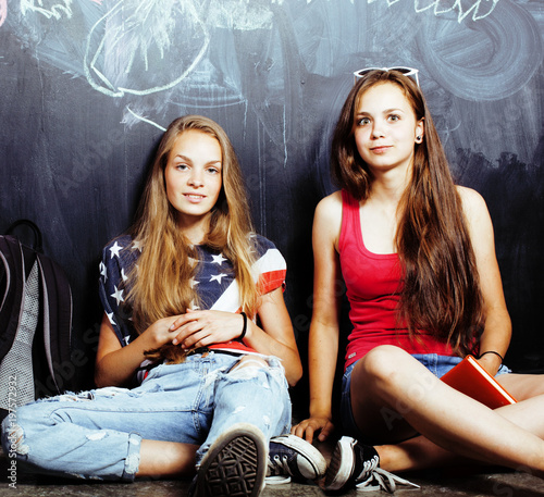 Photo back to school after summer vacations, two teen real girls in classroom with bla