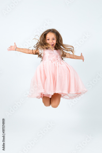 Fotografie, Obraz  Bambina castana in abito rosa che salta