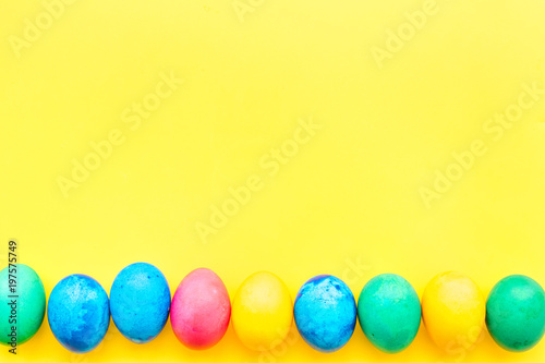 Traditional easter design with colorful eggs on yellow background top view space for text