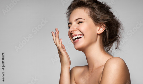 Fotografía  A happy laughing young woman with perfect skin, natural make-up and a beautiful smile