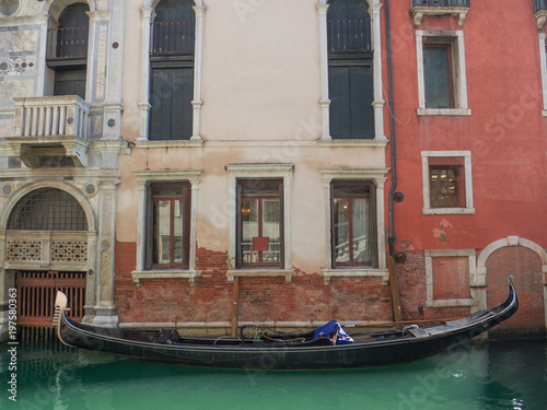 Spoed Foto op Canvas Gondolas traditional gondola moored at the entrance of a palace in a canal in Venice, Italy.