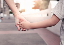 A Parent Holds The Hand Of A S...