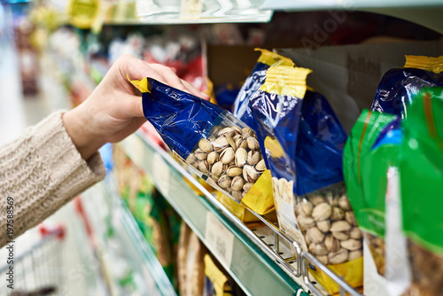 Hand with packing of salted pistachios in store