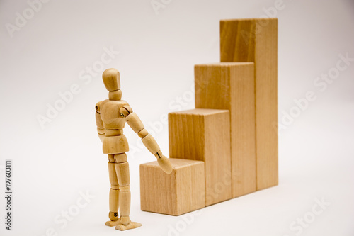 Wooden Man Stands In Front Of A High Staircase And Look Ahead