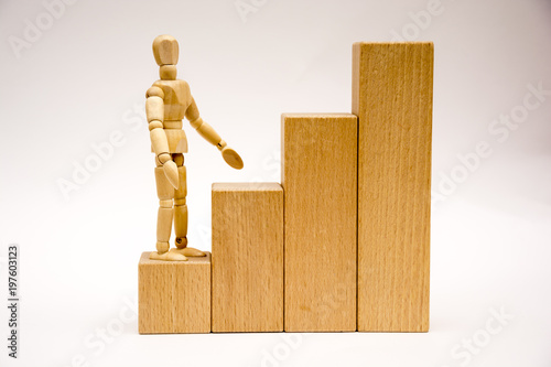 Fotografiet  Wooden man stends on the first step of a high staircase he looks away (front vie