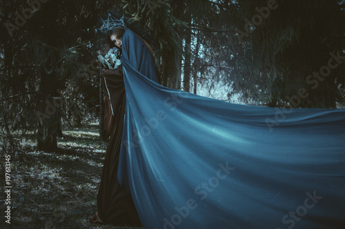 Obraz na plátně Beautiful model is posing in a forest with blue fabric