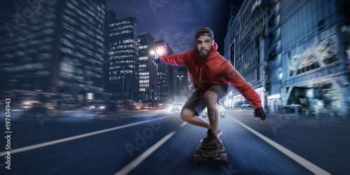 Fotografie, Obraz  Hipster man rides on a longboard in the streets at night