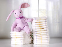 Toy Bunny Sitting On Stack Of Disposable Diapers Or Nappies