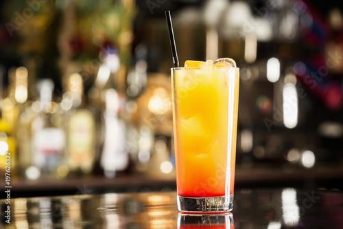 Fotografija  Closeup glass of tequila sunrise cocktail at bar background.