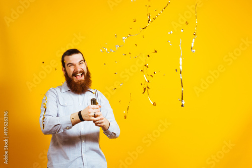 Obraz Portrait of Screaming bearded hipster man throwing confetti over yellow background, copyspace, free space for text. Businessman throwing confetti in the air. - fototapety do salonu