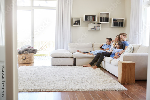 Valokuva  Family Sitting On Sofa At Home Watching TV Together