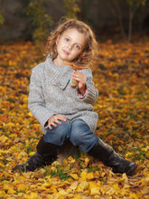Little Girl Playing In The Park In Autumn