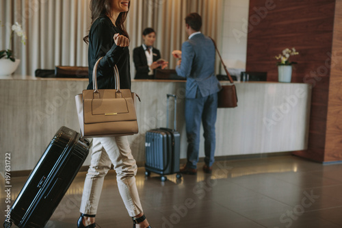Female guest walks inside a hotel lobby