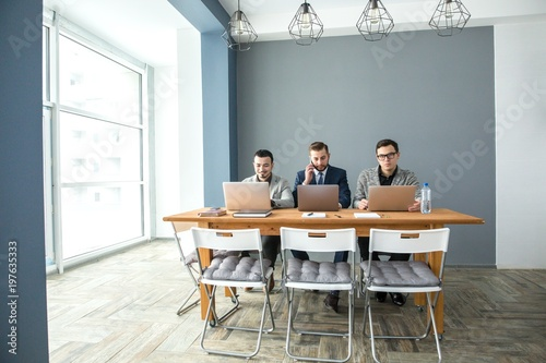 Fotografia  Three businessmen working at laptops sitting at the table