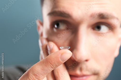 Fotomural  Young man putting contact lens in his eye on color background