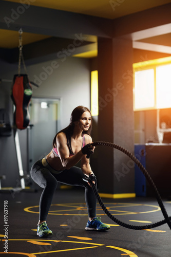 Keuken foto achterwand Ontspanning Athletic young woman doing crossfit exercises with a rope.