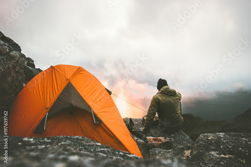 Tuinposter Kamperen Man traveler alone enjoying sunset in mountains sitting near of tent camping gear outdoor Travel adventure lifestyle concept hiking wanderlust vacations