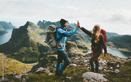Obraz Happy couple giving five hands hiking with backpack in mountains Travel lifestyle adventure concept family together spending active wanderlust vacations - fototapety do salonu