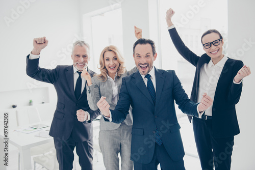 Fotografie, Obraz  Four, attractive, stylish, cheerful business people in suits celebrating victory