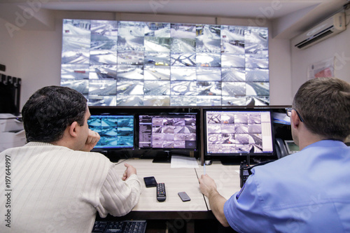 Photo  Two men observe display monitors with live images from road traffic in Bucharest