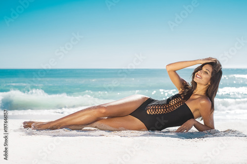Smiling woman lying on sand