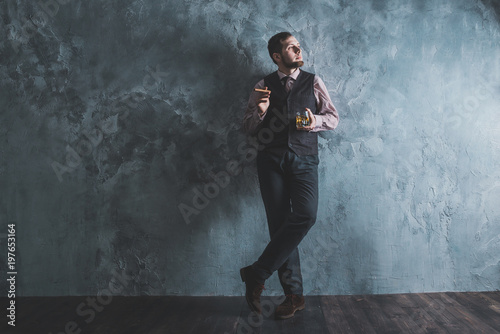 Fototapety, obrazy: Man in vest standing, leaning against the wall, holding a glass. Full lenght portrait