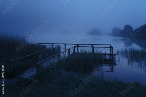 mysterious wooden jetty on lake at night
