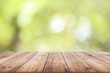 Wooden plank with natural green bokeh background