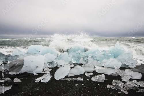 Scenic view of waves splashing on glaciers at beach against sky
