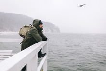 Man With Backpack Looking At Sea While Standing By Railing
