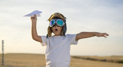 Little boy wearing helmet and dreams of becoming an aviator while playing a pape Wallpaper Mural