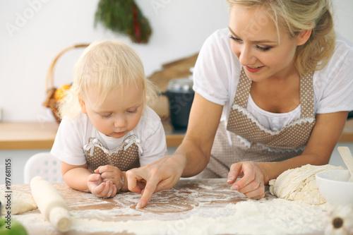 Plakat Mała dziewczynka i jej blondynki mama w czerwonych fartuchach bawić się i śmia się podczas gdy ugniatający ciasto w kuchni. Domowe ciasta na chleb, pizzę lub upiecz ciasteczka