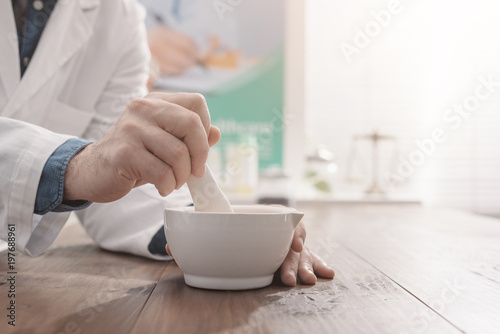 Pharmacist grinding a preparation using a pestle