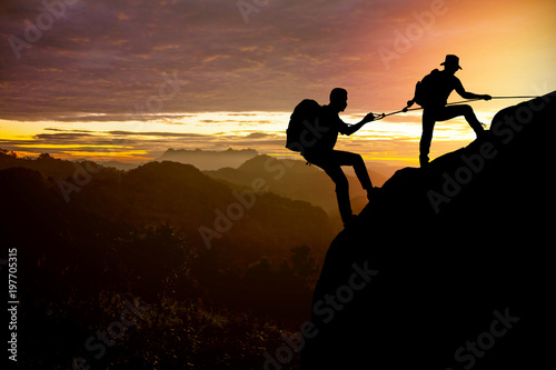 Fototapety, obrazy: Silhouette climber helping teammate climb man with the backpack reached out a helping hand to his friend.
