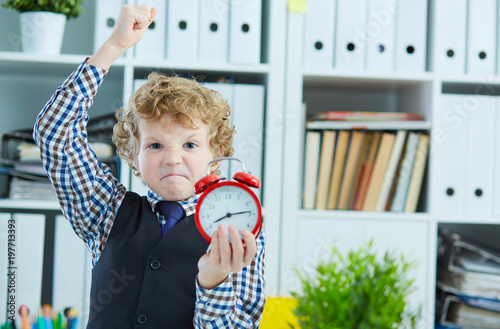 Angry boy trying to punch an alarm clock, standing in office Poster