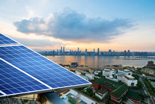 Solar Panels With Cityscape Of...
