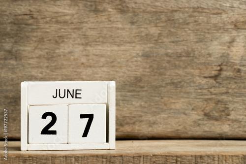 Fényképezés  White block calendar present date 27 and month June on wood background