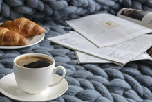 A Cup Of Coffee, Croissants And Magazines On A Knitted Plaid