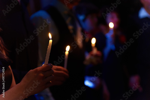 Photo People hold candles light at dark scene