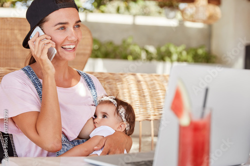 Valokuva  Young happy mother in stylish cap and casual clothing, breastfeeds her little ch