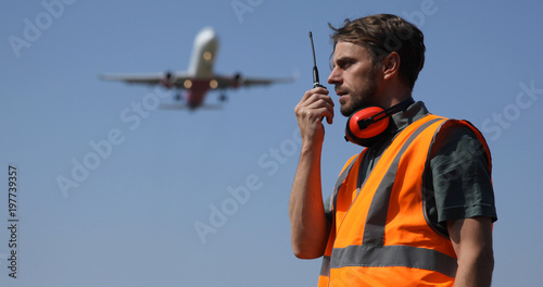 Photo Airport Ground Worker Man Communicating Over Walkie Talkie with Air Traffic Cont