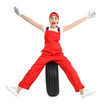Female mechanic in uniform with car tire on white background