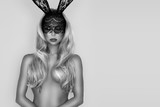 Beautiful, sexy, naked woman in Halloween, Easter bunny costume and black lace mask, standing on white background