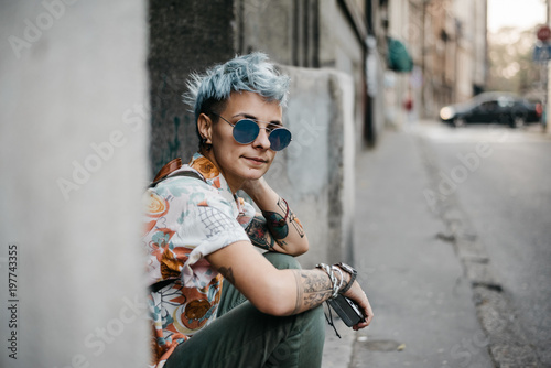 Modern young woman with blue short hair and sunglasses - street style
