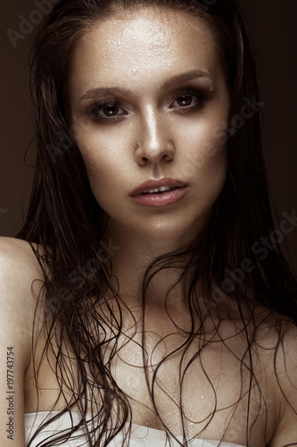Obraz na plátně  Beautiful girl with a bright make-up and wet hair and skin