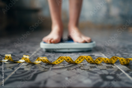 Female feet on the scales, measuring tape Fototapeta