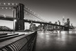 Brooklyn Bridge Park boardwalk in evening with the skyscrapers of Lower Manhattan, East River, and the Brooklyn Bridge in Black & White. Brooklyn, New York City